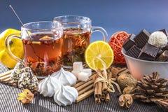 Två glass kopp te med citronen och sötsaker arkivfoto