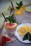 Två glass koppar av vatten med den röda apelsinen, citronen, mintkaramellen och is Fr Royaltyfria Foton