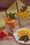 Två glass koppar av vatten med den röda apelsinen, citronen, mintkaramellen och is Fr Arkivbild