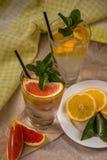 Två glass koppar av vatten med den röda apelsinen, citronen, mintkaramellen och is Fr Royaltyfri Bild