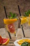 Två glass koppar av vatten med den röda apelsinen, citronen, mintkaramellen och is Fr Royaltyfri Fotografi