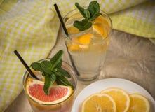 Två glass koppar av vatten med den röda apelsinen, citronen, mintkaramellen och is Fr Arkivfoto