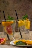 Två glass koppar av vatten med den röda apelsinen, citronen, mintkaramellen och is Fr Royaltyfria Bilder