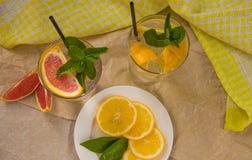 Två glass koppar av vatten med den röda apelsinen, citronen, mintkaramellen och is Fr Royaltyfri Foto