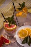 Två glass koppar av vatten med den röda apelsinen, citronen, mintkaramellen och is Fr Arkivfoton