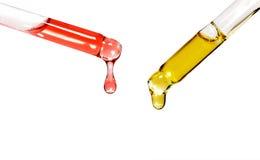 Två glass pipetter med kulöra oljor det Royaltyfri Fotografi