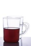 Två glass tekoppar, ett av dem som är tomma och en med iso för svart te Fotografering för Bildbyråer