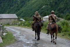 Två gränsbevakningar på hästar i byn Mazeri, som lokaliserade royaltyfria bilder