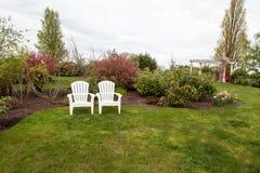 Två gräsmattastolar i en trädgård Royaltyfri Foto