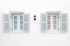 Två gråa fönster med den blåa gardinen och rosa curtai Royaltyfri Bild