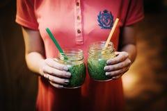 Två gröna coctailar i händer Närbild fotografering för bildbyråer