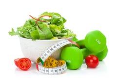 Två gröna dumbells, måttband och sund mat Kondition och H arkivbild
