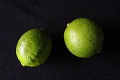 Två gröna limefrukter mot svart bakgrund royaltyfri fotografi