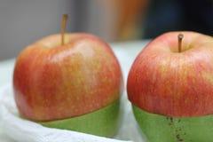 Två GRÖNA måsta-färgade äpplen - som ÄR RÖDA & Royaltyfri Fotografi