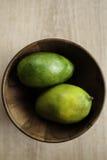 Två gröna mogna mango i träbunken Arkivfoto