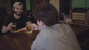 Två grabbar dricker öl, medan sitta på en tabell i en bar Grabbar som har gyckel som dricker tillsammans öl Fritid i en ölbar stock video