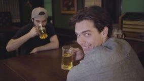 Två grabbar dricker öl som klirrar exponeringsglas, medan sitta på en tabell i en bar Grabbar som har gyckel som dricker tillsamm arkivfilmer