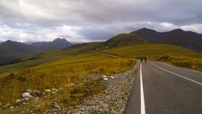Två grabbar fotvandrar vid vägen i Kaukasus berg Hake-fotvandra 4K UHD arkivfilmer