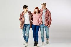 Två grabbar och en flicka i stilfull ljus färgrik kläder går och ler på den vita bakgrunden i studion royaltyfri foto