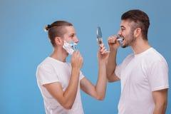 Två grabbar rakar skägg och borstar tänder, medan stående fasadbeklädnad och se spegeln arkivfoto