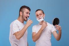 Två grabbar sköter sig Ett av dem borstetänder och de andra rakningarna uppsöker En torr frukost i en sked Royaltyfri Foto