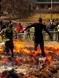 Två grabbar som hoppar över brand arkivbild