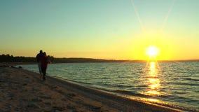 Två grabbar som joggar längs stranden arkivfilmer