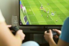 Två grabbar som spelar den imaginära multiplayer fotboll- eller fotbollleken Arkivbilder