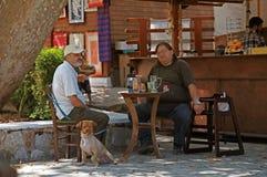 Två grekiska manar sitter på en lantlig utomhus- cafe (Crete, Grekland) Royaltyfri Fotografi