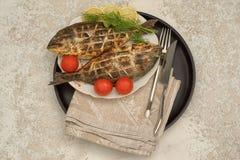 Tv? grillad doradofisk p? en platta och ett svart cirkelmagasin med med citronen och tomater, royaltyfria foton