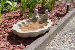 Två grodastatyer på en liten vattenpöl som sitter förutom en gångbana i en trädgård arkivfoton