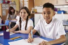 Två grundskola för barn mellan 5 och 11 årelever i klassrumet som ser till kameran Royaltyfri Bild