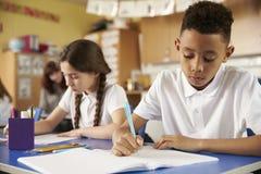 Två grundskola för barn mellan 5 och 11 årelever på deras skrivbord i grupp, slut upp Fotografering för Bildbyråer