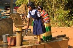 Två grundskola för barn mellan 5 och 11 årflickor tvättar deras hand och deras disk, innan de tar Mitt--dagen mål i en grundskola arkivfoton