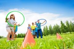 Två grupp av ungar som spelar med hulabeslag royaltyfri foto