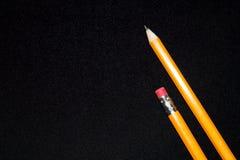 Två gula blyertspennor på suddig bakgrund för mörk svart brevpapper Kontorshjälpmedel äganderätt för home tangent för affärsidé s Royaltyfria Bilder