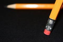 Två gula blyertspennor på suddig bakgrund för mörk svart brevpapper Kontorshjälpmedel äganderätt för home tangent för affärsidé s Arkivbilder