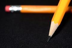 Två gula blyertspennor på suddig bakgrund för mörk svart brevpapper Kontorshjälpmedel äganderätt för home tangent för affärsidé s Royaltyfria Foton