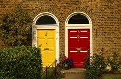 Två gula georgiska dörrar för tappning och röda färger i Dublin, Irela arkivbilder