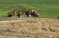 Två gula grävskopor och stor gul lastbil royaltyfri bild
