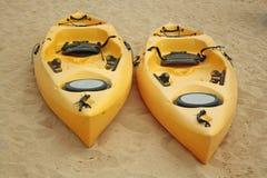 Två gula kajaker som vilar på stranden Arkivbild