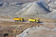 Två gula lastbilar i en kolgruva Royaltyfri Fotografi