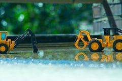Två gula leksakforklines spelar i gården med lite vatten efter vårregn fotografering för bildbyråer