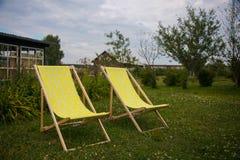 Två gula stolar i sommargräsplanen arbeta i trädgården för kopplar av arkivfoto