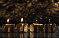 Två guld- adventstearinljus som tänds med bokehbakgrund Arkivfoto