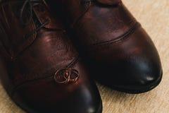 Två guld- breda vigselringar som lokaliserades på mäns skor, gjorde av brunt läder royaltyfri bild