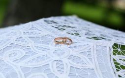 Två guld- cirklar för brud- är på vitt tyg Royaltyfri Bild