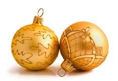 Två guld- julbollar som isoleras på en vit Arkivbild