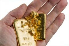 Två guld- stänger och flera guld- klumpar på gömma i handflatan arkivbild