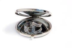 Två guld- vigselringar i en liten rund glass spegel Fotografering för Bildbyråer